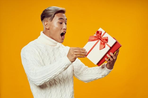 Aufgeregter asiatischer mann mit einer geschenkbox