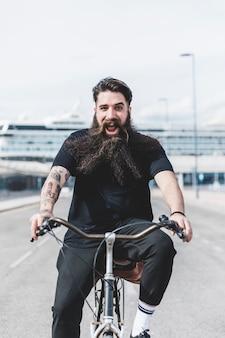 Aufgeregter bärtiger junger mann, der das fahrrad fahren genießt