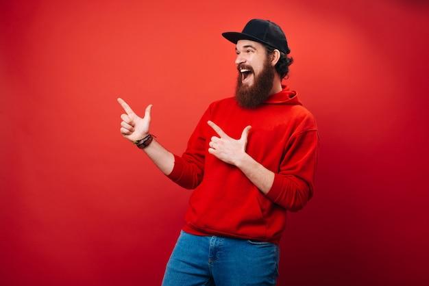 Aufgeregter bärtiger mann im roten kapuzenpulli, zeigt mit dem finger weg, vorbei