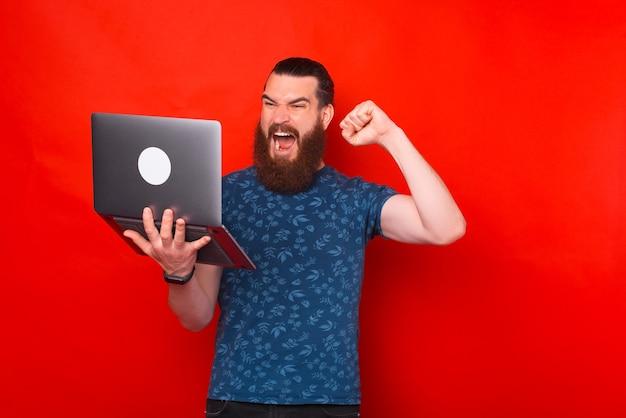 Aufgeregter bärtiger mann macht die gewinnergeste und schreit, während er auf den laptop schaut, den er hält.