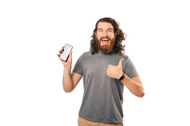 Aufgeregter bärtiger mann mit langem, gewelltem haar, das ein telefon hält und daumen nach oben zeigt.