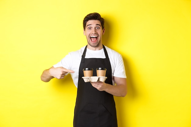 Aufgeregter barista in schwarzer schürze, der mit den fingern auf kaffeetassen zum mitnehmen zeigt und vor gelbem hintergrund glücklich steht.