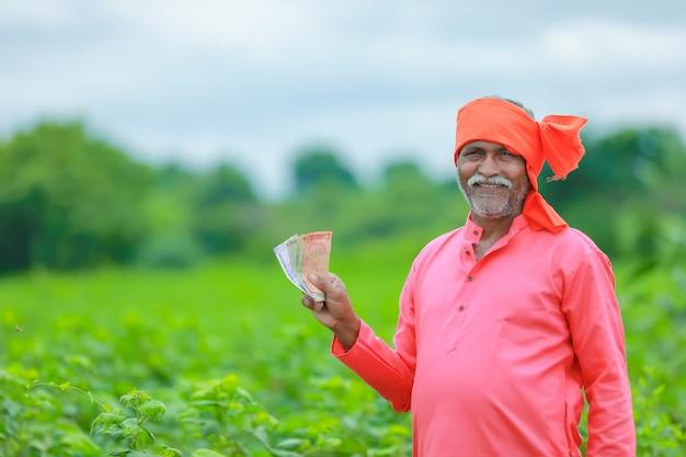Aufgeregter bauer, der indische rupiennoten hält