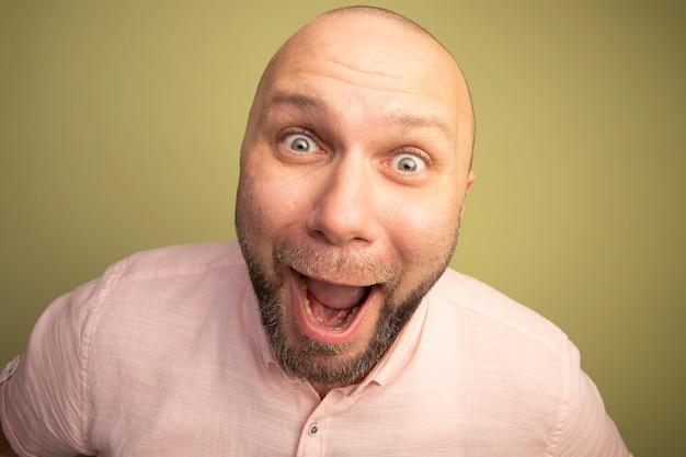 Aufgeregter blick geradeaus kahler mann mittleren alters, der rosa t-shirt trägt, das auf olivgrün isoliert wird