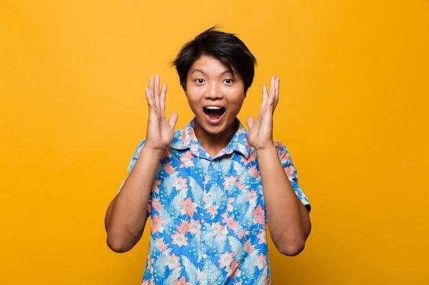 Aufgeregter emotionaler junger asiatischer mann, der isoliert über gelbem raum aufwirft.