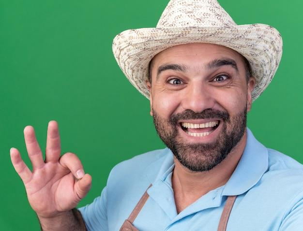 Aufgeregter erwachsener kaukasischer männlicher gärtner mit gartenhut, der ein gutes zeichen mit blick auf die kamera gestikuliert