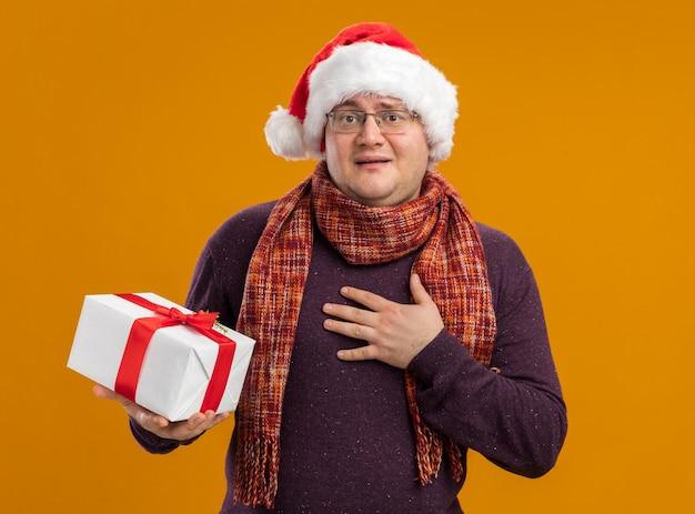 Aufgeregter erwachsener mann, der brille und weihnachtsmütze mit schal um hals hält, der geschenkpaket hält, das kamera betrachtet, die dankesgeste lokalisiert auf orange hintergrund tut