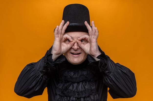 Aufgeregter erwachsener mann mit zylinder und in schwarzem gothic-hemd, der durch die finger schaut