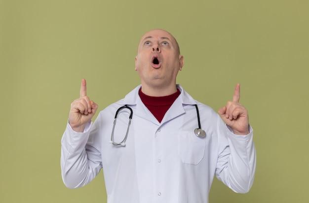 Aufgeregter erwachsener slawischer mann in arztuniform mit stethoskop, das nach oben schaut und zeigt