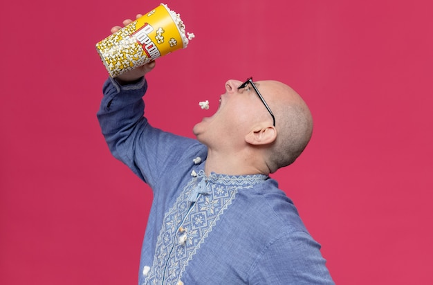 Aufgeregter erwachsener slawischer mann in blauem hemd mit optischer brille, der popcorn-eimer hält und isst