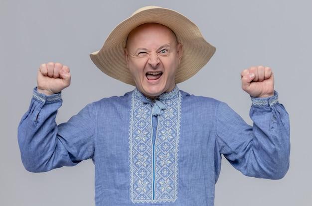 Aufgeregter erwachsener slawischer mann mit strohhut und in blauem hemd, der seine fäuste hochhebt
