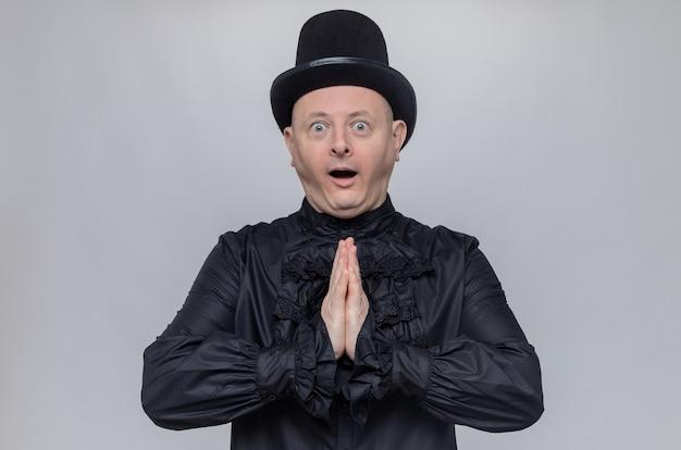 Aufgeregter erwachsener slawischer mann mit zylinder und in schwarzem gothic-hemd, der die hände zusammenhält und