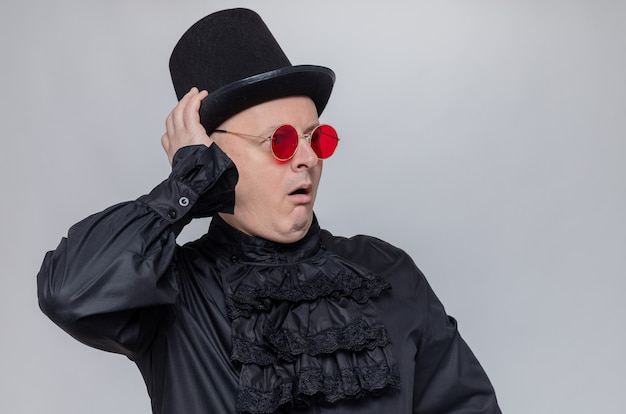 Aufgeregter erwachsener slawischer mann mit zylinder und sonnenbrille in schwarzem gothic-hemd, der auf die seite schaut