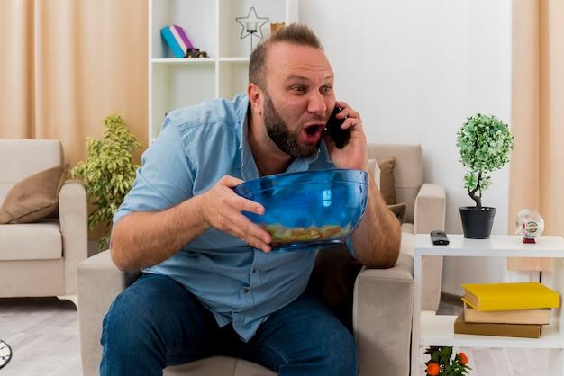 Aufgeregter erwachsener slawischer mann sitzt auf sessel, der am telefon spricht und schüssel des chips innerhalb des wohnzimmers hält