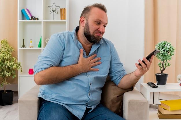 Aufgeregter erwachsener slawischer mann sitzt auf sessel und legt hand auf brust und betrachtet telefon im wohnzimmer