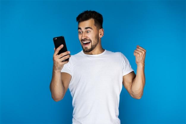Aufgeregter europäischer kerl passt auf das mobiltelefon auf
