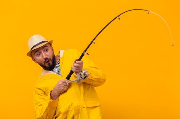 Aufgeregter fischer, der auf der angelrute zieht