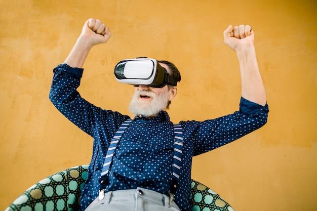 Aufgeregter fröhlicher älterer bärtiger mann im stilvollen dunkelblauen hemd und in den hosenträgern, mit vr 3d brille und film- oder fußballspiel mit lächeln und geballten fäusten