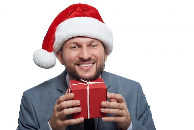 Aufgeregter fröhlicher geschäftsmann, der lächelnd eine kleine weihnachtsgeschenkbox an sein gesicht hält