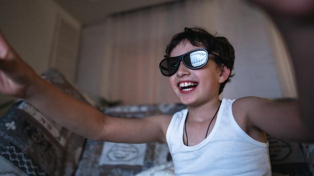 Aufgeregter fröhlicher junge in der 3d-brille, die einen film sieht