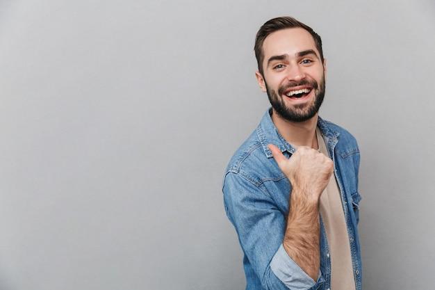 Aufgeregter fröhlicher mann, der hemd trägt, das über grauer wand lokalisiert ist und auf kopienraum zeigt