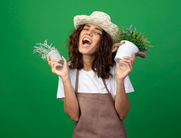 Aufgeregter gärtner der jungen frau in der uniform, die gartenhut hält, der blumen in den blumentöpfen hält, die auf grün lokalisiert werden