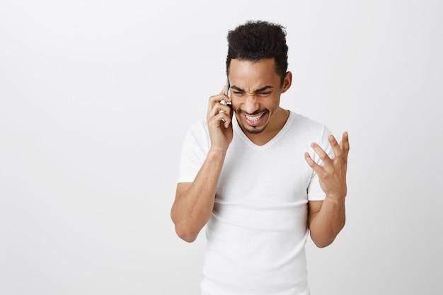 Aufgeregter glücklicher afroamerikanischer mann, der am telefon spricht und fröhlich lächelt