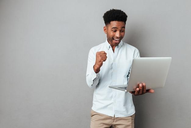 Aufgeregter glücklicher afroamerikanischer mann, der laptop-computer betrachtet