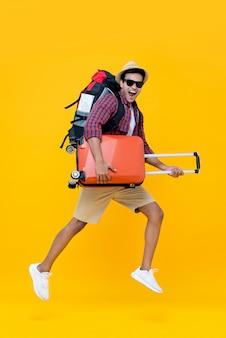 Aufgeregter glücklicher junger asiatischer manntourist mit dem gepäckspringen