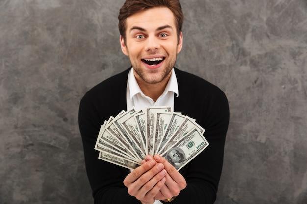 Aufgeregter glücklicher junger geschäftsmann, der geld hält