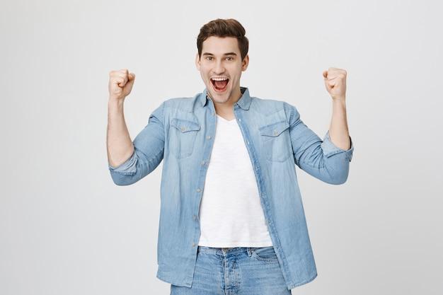 Aufgeregter glücklicher junger mann erreicht erfolg, faustpumpe freut sich