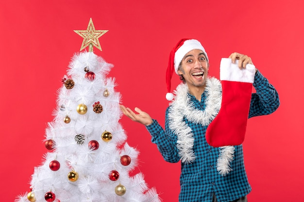 Aufgeregter glücklicher junger mann mit weihnachtsmannhut in einem blauen gestreiften hemd und halten weihnachtssocke nahe weihnachtsbaum