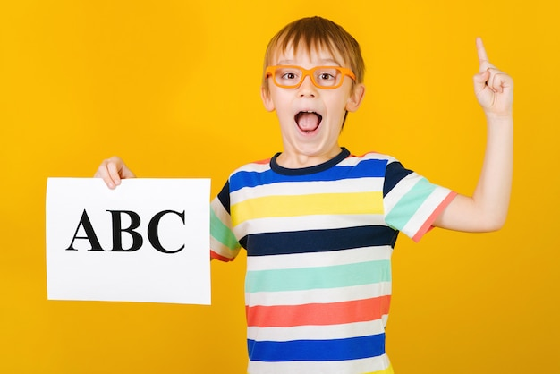 Aufgeregter glücklicher kleiner junge, der briefe lernt. junge hält abc-karte. sprachtherapeut unterricht.