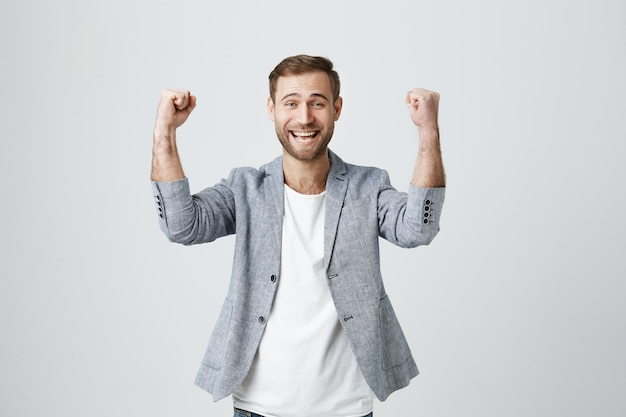 Aufgeregter glücklicher mann, der sieg feiert
