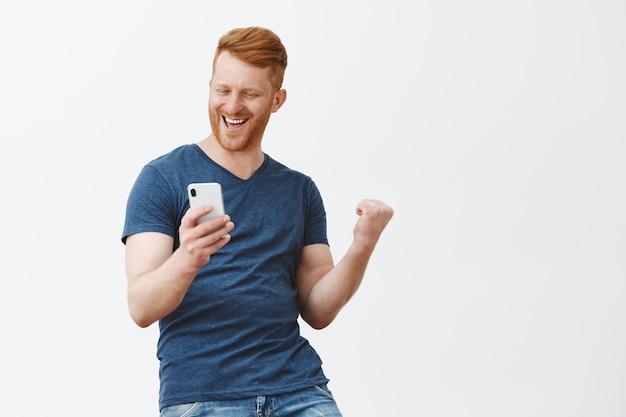 Aufgeregter glücklicher und feiernder hübscher rothaariger mann mit borste, faust in siegesgeste hochhebend, smartphone haltend