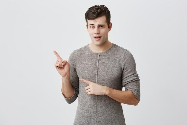 Aufgeregter gutaussehender kerl zeigt mit dem zeigefinger am kopierplatz für werbung oder werbetext an. erstaunlich attraktiver stilvoller mann mit dunklem haar und blauen augen zeigt in die ferne