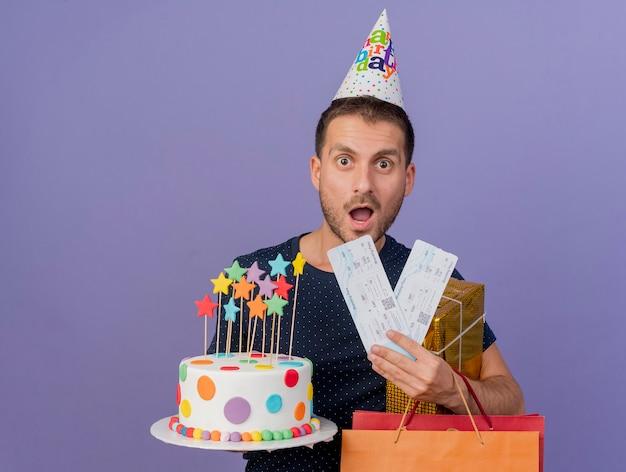 Aufgeregter gutaussehender mann, der geburtstagskappe hält, hält geburtstagskuchenpapier-einkaufstasche-geschenkbox und flugtickets lokalisiert auf lila wand