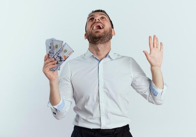 Aufgeregter gutaussehender mann hält geld und hebt hand, die isoliert auf weißer wand schaut