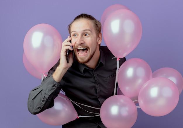 Aufgeregter gutaussehender mann steht mit heliumballons, die am telefon lokalisiert auf lila wand sprechen
