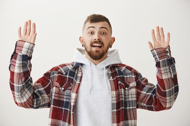 Aufgeregter hipster, der die hände in der hingabe erhebt und erstaunt aussieht
