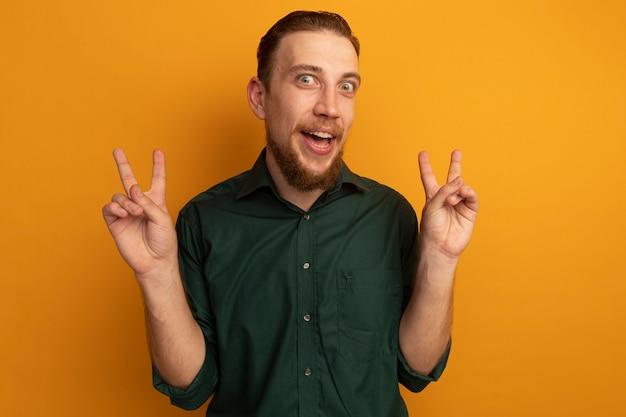 Aufgeregter hübscher blonder mann gestikuliert siegeshandzeichen mit zwei händen, die auf orange wand lokalisiert werden