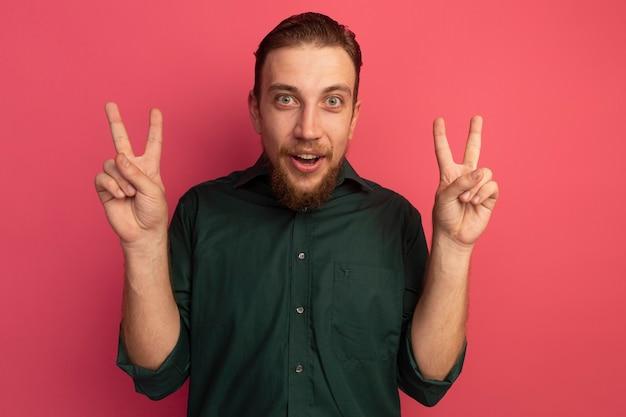 Aufgeregter hübscher blonder mann gestikuliert siegeshandzeichen mit zwei händen, die auf rosa wand lokalisiert werden
