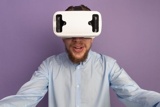 Aufgeregter hübscher blonder mann mit vr headset, der lokalisiert auf lila wand steht