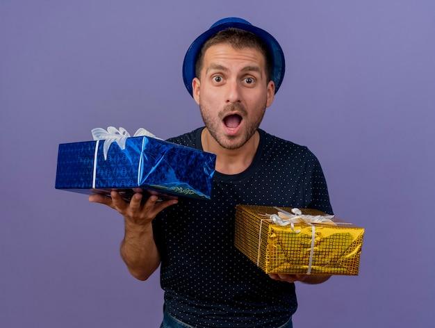 Aufgeregter hübscher kaukasischer mann, der blauen hut trägt, hält geschenkboxen lokalisiert auf lila hintergrund mit kopienraum