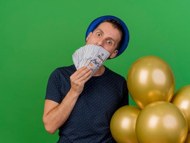 Aufgeregter hübscher kaukasischer mann, der blauen parteihut trägt, hält heliumballons und geld lokalisiert auf grünem hintergrund mit kopienraum