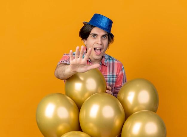 Aufgeregter hübscher kaukasischer mann, der blauen parteihut trägt, steht mit heliumballons