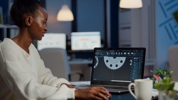 Aufgeregter industriearchitekt der schwarzen frau, der an modernen cad-programmüberstunden arbeitet und im start-up-büro sitzt. wirtschaftsingenieur, der die idee eines prototyps auf dem pc studiert, der cad-software auf dem gerätedisplay zeigt