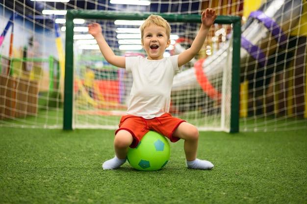 Aufgeregter junge, der auf ball sitzt