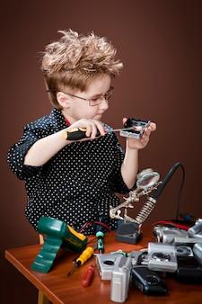 Aufgeregter junge lächelt und repariert kameras.