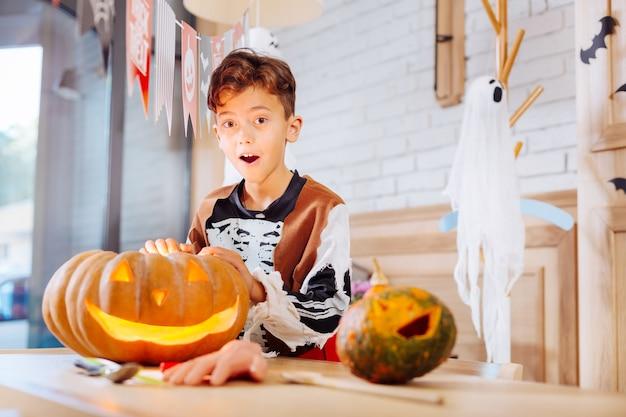 Aufgeregter junge. netter lustiger junge, der das gefühlskelettkostüm aufgeregt trägt, während er nahe geschnitztem halloween kürbis steht